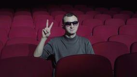 坐在舒适的红色椅子在黑暗的戏院剧院和做与手指的唯一人胜利标志 股票视频