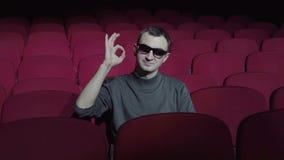 坐在舒适的红色椅子在黑暗的戏院剧院和显示好标志的唯一人 影视素材