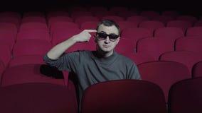 坐在舒适的红色椅子的唯一人在黑暗的戏院剧院和扭转她的手指在她的寺庙 股票视频