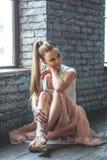 坐在舞蹈演播室的年轻舞蹈家 图库摄影
