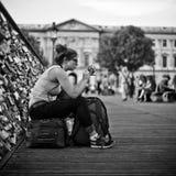 坐在艺术桥梁的妇女在巴黎 免版税库存照片