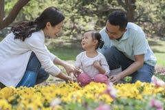 坐在花园里的家庭。 免版税库存照片