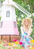 坐在花园里的愉快的美女 免版税库存图片