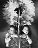 坐在花圈下的两个孩子拿着圣诞节故事书(所有人被描述不是更长的生存和没有庄园exi 免版税库存照片