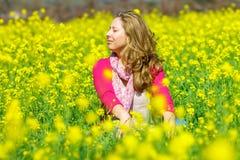 坐在花的女孩 图库摄影