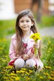 坐在花的领域的女孩 免版税库存照片