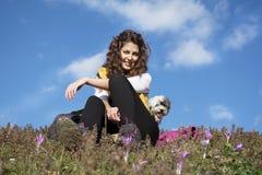 坐在花的领域的少妇与室外她的白色的狗的 免版税库存照片