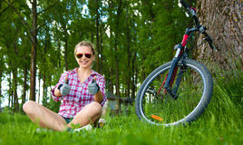 坐在草和显示赞许的年轻骑自行车者打手势 免版税库存照片