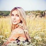 坐在草和花中的美丽的微笑的女孩 库存照片