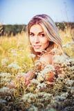 坐在草和花中的美丽的微笑的女孩 免版税库存照片