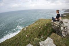 坐在草小山峭壁边缘 库存照片