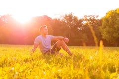 坐在草的一个年轻人 免版税库存照片