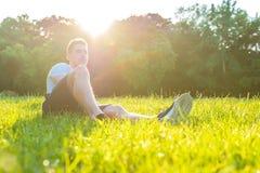 坐在草的一个年轻人 库存照片