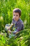 坐在草的严肃的男孩 免版税库存照片