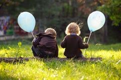 坐在草的兄弟和姐妹拿着蓝色气球 库存照片