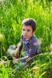 坐在草的哀伤的男孩 库存照片