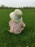 坐在草的小女孩特写镜头在穿草帽和调查距离的公园 库存图片