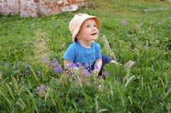 坐在草的小男孩 库存照片