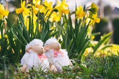 坐在草的愉快的复活节羊羔 免版税库存图片