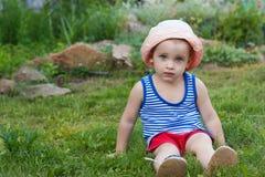 坐在草的男孩外面 调遣结构树 库存图片