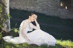 坐在草的美丽的新娘 免版税图库摄影
