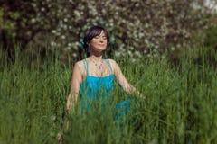 坐在草的美丽的深色的女孩 库存图片
