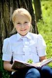 坐在草的逗人喜爱的小女孩在树附近 免版税图库摄影