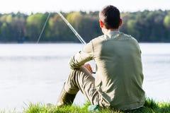 坐在草的钓鱼者在与他的标尺的湖边钓鱼 免版税库存图片