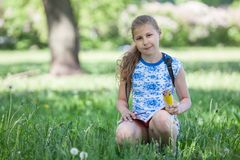 坐在草的青春期前的女孩在有写生簿和铅笔的在手上,拷贝空间公园 图库摄影