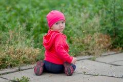 坐在草附近的逗人喜爱的婴孩 免版税库存照片