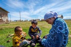 坐在草,吉尔吉斯斯坦的妇女和两个孩子 库存图片