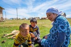 坐在草,吉尔吉斯斯坦的妇女和两个孩子 免版税库存照片