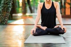 坐在莲花姿势和思考或者祈祷的被集中的女孩 单独少妇实践的瑜伽在木甲板  库存图片