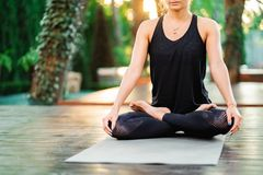 坐在莲花姿势和思考或者祈祷的被集中的女孩 单独少妇实践的瑜伽在木甲板  库存照片