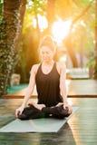 坐在莲花姿势和思考或者祈祷的被集中的女孩 单独少妇实践的瑜伽在木甲板  免版税库存图片