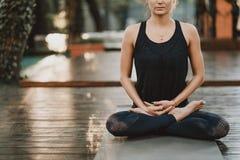坐在莲花姿势和思考或者祈祷的被集中的女孩 单独少妇实践的瑜伽在木甲板  免版税库存照片