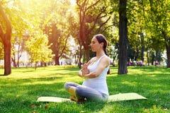 坐在莲花姿势和放松在pa的可爱的孕妇 免版税库存图片