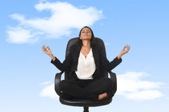 坐在莲花姿势实践的瑜伽和凝思的办公室椅子的美国女商人 免版税库存照片