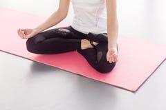 坐在莲花姿势的匿名妇女,做瑜伽 免版税库存照片