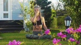 坐在莲花姿势的妇女Pranayama瑜伽呼吸的实践在后院 股票录像