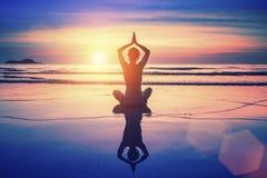 坐在莲花姿势的瑜伽妇女在与反射的海滩在日落期间 免版税库存照片