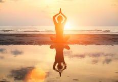 坐在莲花姿势的瑜伽妇女在海滩在日落期间,与反射在水中 免版税库存照片