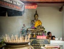 坐在菩萨雕象附近的人 免版税库存图片