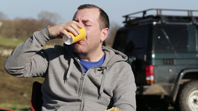 坐在营火旁边,吃面包和喝coffe的人 股票录像