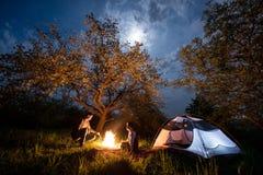 坐在营火的浪漫夫妇游人在帐篷在树下和与月亮的夜空附近 免版税库存照片