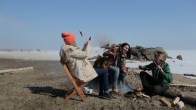 坐在营火附近的一群人 后面架靠背 股票视频