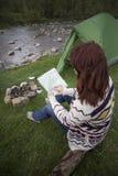 坐在营火附近的女孩在看地图和喝咖啡的露营地 库存照片