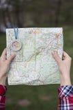 坐在营火附近的女孩在看地图和喝咖啡的露营地 图库摄影