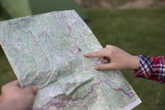 坐在营火附近的女孩在看地图和喝咖啡的露营地 库存图片