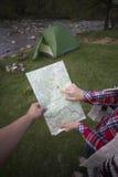 坐在营火附近的女孩在看地图和喝咖啡的露营地 免版税库存照片